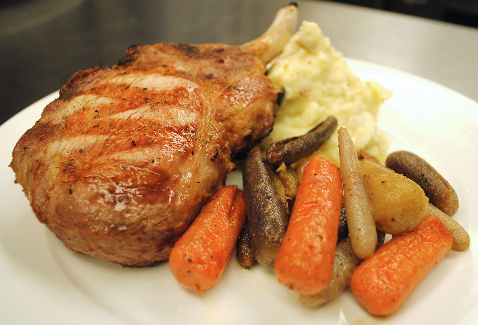 Double Cut Pork Chop with garlic mashed potatoes, baby carrots, and natural pan jus.