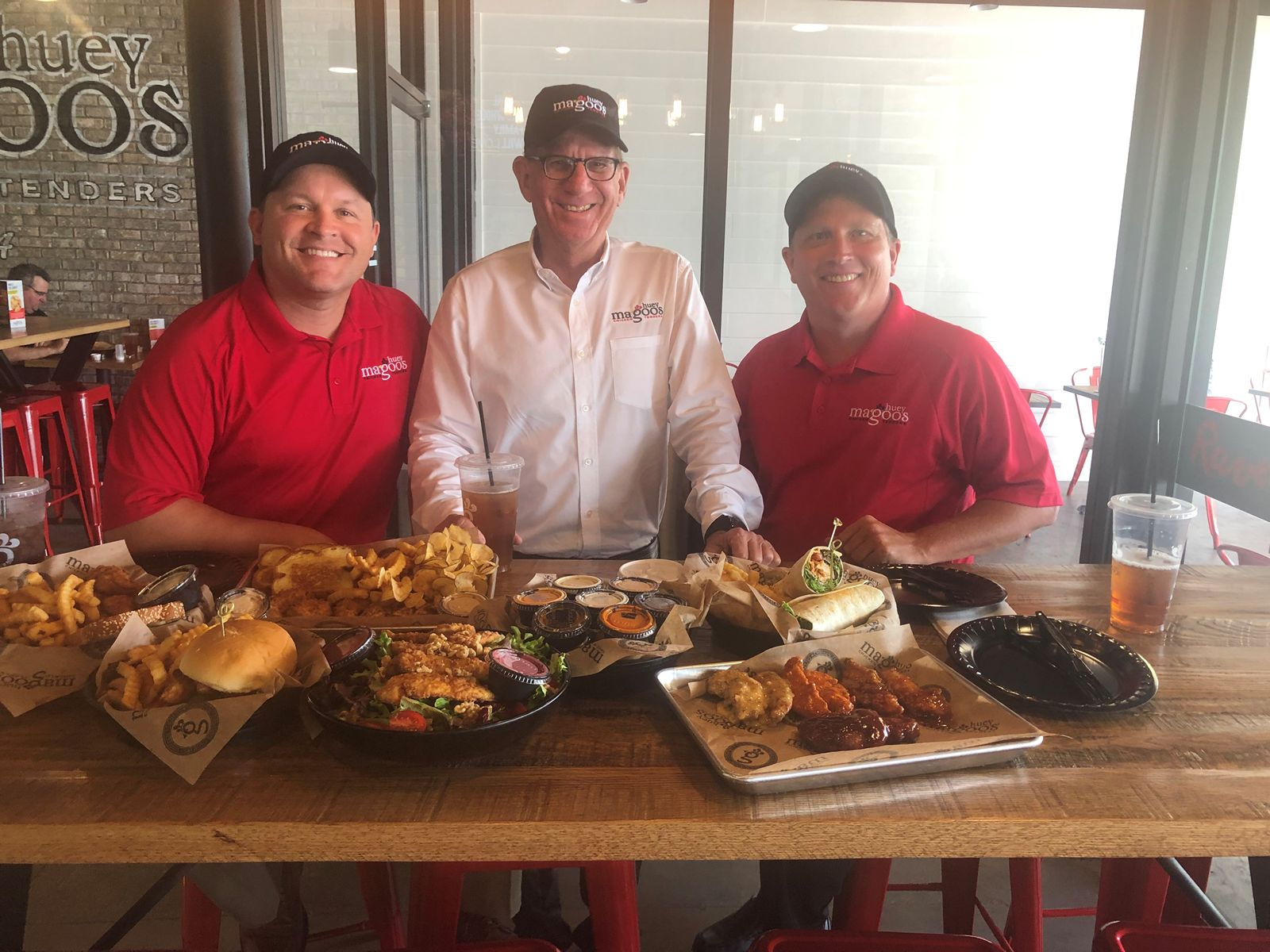 Bryan Pagan with Huey Magoo's President and CEO Andy Howard, and James Connolly.